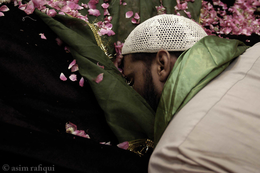 bari imam shrine, islamabad, pakistan 2004: a devotee prostrates himself at the bari imam's grave.  hundreds of housands will arrive at this site during the 5 day annual 'urs' and pray to the holy man for intervention and help with their problems.<br />