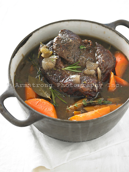 Beef pot roast in a large stock pot, with carrots, bay leaf, onion, celery, and herbs.