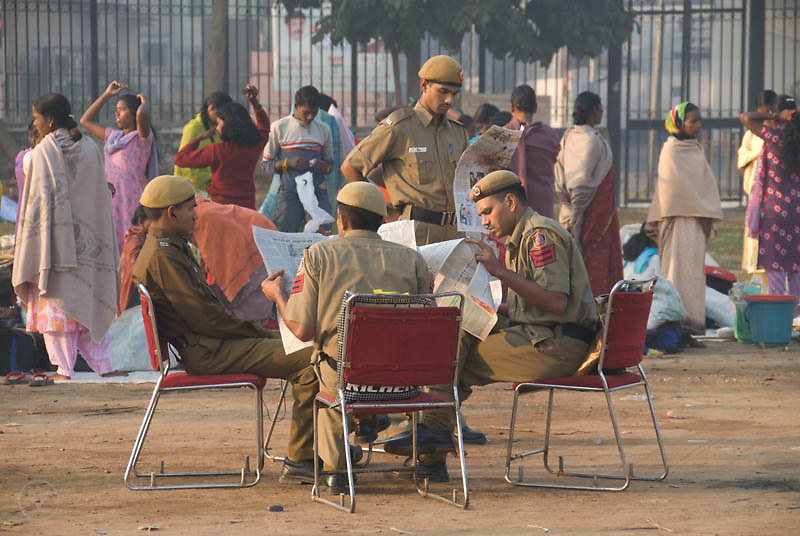 Policemen, seated at a folding table, read the news about the victory of the Janadesh Walk for Land, while participants of the Janadesh march prepare to go home, Ram Lila Grounds, New Delhi, October 30 2007