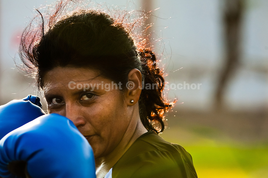 A Peruvian woman practices defense while training in the outdoor boxing school at the Telmo Carbajo stadium in Callao, Peru, 4 April 2013.