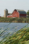 Red wooden barn with gambrel roof, silo; wetlands and pond, North Dakota.