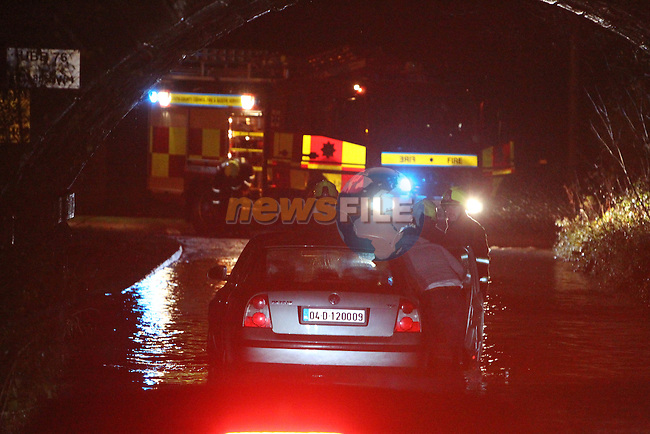 Drogheda Fire service responded to reports of people trapped in flood water under the railway bridge on the Bettystown to  Piltown road outside Drogheda, Members of the fire service assisted the owner of the car to remove it from the flood water..Picture: Fran Caffrey/www.newsfile.ie.