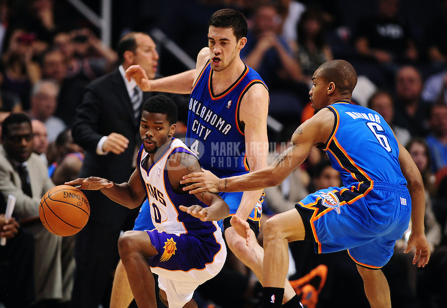 Mar. 30, 2011; Phoenix, AZ, USA; Phoenix Suns guard (0) Aaron Brooks controls the ball under pressure from Oklahoma City Thunder guard (6) Eric Maynor and forward (4) Nick Collison in the second half at the US Airways Center. The Thunder defeated the Suns 116-98. Mandatory Credit: Mark J. Rebilas-