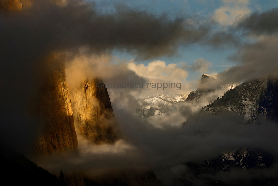 The Tunnel View of approaching storm  in Yosemite National Park. El Capitan monolith shrouded in dark clouds as sunset begins with the famous Half Dome in the background.