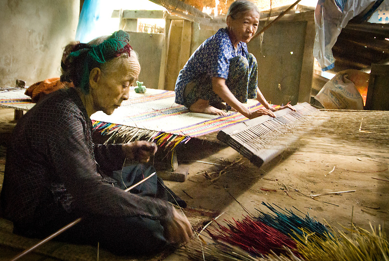 Two elderly Vietnamese women are weaving in a small village outside of Hoi An, Vietnam