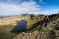 Female hill walker takes in view of Llyn Y Fan Fach from near Waun Lefrith, Black Mountain, Brecon Beacons national park, Wales