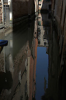 Reflections of buildings in the water of the venetian canals, Venice, Italy.
