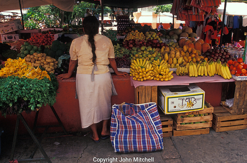 Woman selling fruit and produce at the market in Tepoztlan, Morelos, Mexico. Tepoztlan has been designated a pueblo magico or magical town.