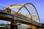 NIEUWEGEIN - Bij het begin van de avond werkt een medewerker van bouwcombinatie KWS - Mercon aan de afbouw van de nieuwe 800 ton zware Overeindsebrug. Nadat de oude stalen boogbrug onlangs van zijn plaats was gevijzeld en afgevoerd, is de nieuwe brug met hulp van 2 kranen op pontons op zijn plek gelegd. De 140 meter lange brug is ontworpen door Studio SK en gebouwd op de werf van Mercon in Gorinchem, waarna deze over het water naar het Lekkanaal is vervoerd. De renovatie van de Overeindsebrug is onderdeel van het project KARGO (Kunstwerken Amsterdam-Rijnkanaal Groot Onderhoud) waarbij Rijkswaterstaat acht stalen bruggen vernieuwd. COPYRIGHT TON BORSBOOM