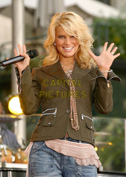 JESSICA SIMPSON.Performs on Good Morning America's Summer Concert Series, Bryant Park, New York City, New York .August 6, 2004 .half length, singing, stage, concert, gig, brown zipper, scarf, beads, necklace, khaki, hands up, gesture.www.capitalpictures.com.sales@capitalpictures.com.©Capital Pictures