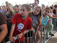 From left, Eden and Maya Block with their friend Ninie Bocock strain to watch rock legend Bruce Springsteen play during a free concert held Tuesday afternoon at the nTelos Wireless Pavilion in Charlottesville, Va.