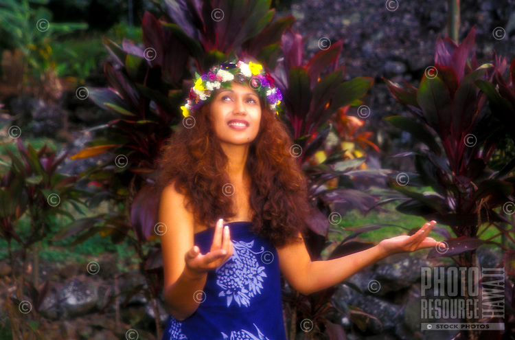Polynesian woman in haku lei with arms open in a nature setting
