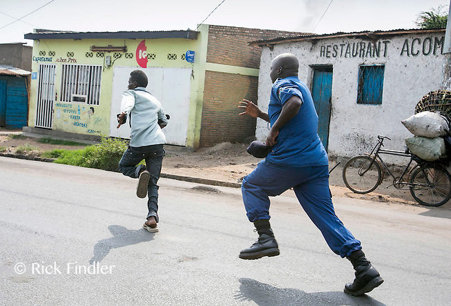 Bujumbura, BURUNDI  05/06/15 The protester makes a run for it from the police in the Musaga neighbourhood in Bujumbura, Burundi on what was supposed to be voting day for parliamentary and local elections. However President Nkurunziza has delayed this process - which was greeted by even more protesting which saw one protester confirmed shot dead by police. Demonstrations have been against President Pierre Nkurunziza trying for a controversial third term as leader. Approximately 90,000 people have fled the unrest which has seen 41 protesters killed by police and army officers. Rick Findler / Story Picture Agency