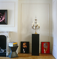 A pair of pop portraits of Freud lean against the wall of the living room either side of a crystal candelabra on top of a pedestal