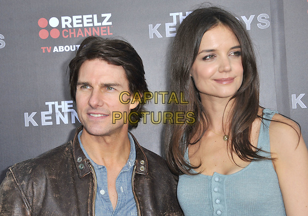 "TOM CRUISE & KATIE HOLMES.attending the World Premiere of ""The Kennedys"" at The Academy of Motion Pictures Arts And Sciences, Samuel Goldwyn Theater in Beverly Hills, California, USA, March 28th, 2011..portrait headshot husband wife married couple brown leather jacket green blue dress buttons vest sleeveless shirt  S initial necklace gold letter                                                                                .CAP/RKE/DVS.©DVS/RockinExposures/Capital Pictures."