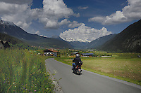 Motor cyclist on country lane passing spring meadows driving towards Tarranz. Imst district, Tyrol, Tirol, Austria.
