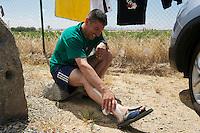 """Bergarbeiterstreik in Spanien.<br />Am 5. Juli 2012 erreichten 200 Bergarbeiter mit dem """"Marcha Negra"""" (der Schwarze Marsch) nach 14 Tagen und 381,7 Kilometer Marsch die Ortschaft Sanchidrian in der Provinz Avila. Am 11. Juli 2012 wollen die Mineros in Madrid eintreffen und vor das Wirtschaftsministerium gehen.<br />Mit dem Marcha Nagra und dem seit Mai andauernden Streik der Mineros soll die Regierung gezwungen werden, die Kuerzung von 64% der Bergbaufoerderung zurueck zu nehmen. Die Kuerzung bedeutet das Aus fuer den spanischen Bergbau und tausende Bergarbeiter sind von Arbeitslosigkeit bedroht.<br />Im Bild: Ein Minero erholt sich von den Strapazen und kuehlt einen Fuss.<br />5.7.2012, Sanchidrian/Spanien<br />Copyright: Christian-Ditsch.de<br />[Inhaltsveraendernde Manipulation des Fotos nur nach ausdruecklicher Genehmigung des Fotografen. Vereinbarungen ueber Abtretung von Persoenlichkeitsrechten/Model Release der abgebildeten Person/Personen liegen nicht vor. NO MODEL RELEASE! Don't publish without copyright Christian-Ditsch.de, Veroeffentlichung nur mit Fotografennennung, sowie gegen Honorar, MwSt. und Beleg. Konto:, I N G - D i B a, IBAN DE58500105175400192269, BIC INGDDEFFXXX, Kontakt: post@christian-ditsch.de.<br />Urhebervermerk wird gemaess Paragraph 13 UHG verlangt.]"""