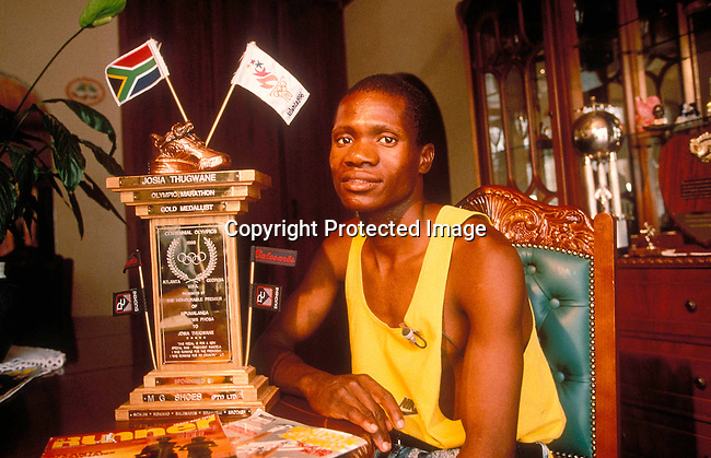 PETHUGJ05552.Personality. Athletics. Josiah Thugwane sitting at a table with a trophy in front of him. 97.©Per-Anders Pettersson/iAfrika Photos