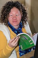 South Africa, Cape Town.  Visually-impaired Albino Student Holding Student Workbook.  Athlone School for the Blind.