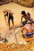 Mucajai, Roraima State, Brazil. Three goldminers at work digging.