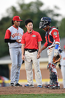 Brooklyn Cyclones trainer Kiyoshi Tada checks on catcher Adrian Abreu (2) as pitcher Marcos Molina (29) looks on during a game against the Batavia Muckdogs on August 9, 2014 at Dwyer Stadium in Batavia, New York.  Batavia defeated Brooklyn 4-2.  (Mike Janes/Four Seam Images)