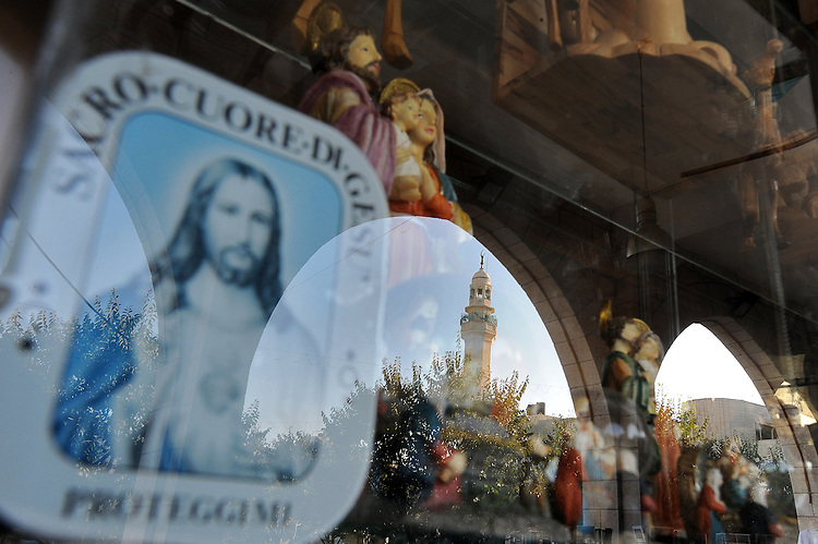A mosque minaret is reflected in a Christian souvenirs shop in Bethlehem, West Bank. The city is believed to be the birth place of Jesus Christ.