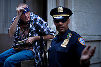 A protester is interrupted by a police officer as he does a performance while protesters of the Occupy Wall Street movement celebrate their first anniversary with marches and confrontations with the New York police where 150 protesters have been arrested during weekend celebrations in Manhattan.  Photo by Eduardo Munoz Alvarez / VIEWpress.