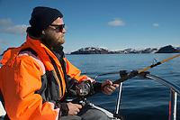Mann på havfiske en flott vårdag. ---- Man fishing from boat.