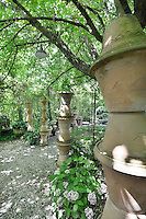 A gravelled garden with stacks of terracotta pots shaded by the foliage from trees.