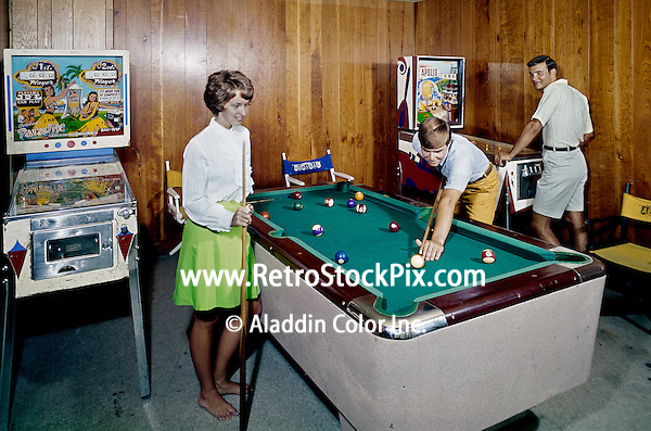 Couple shooting pool and a man playing pin ball in the Admiral Motel game room. 1960's.