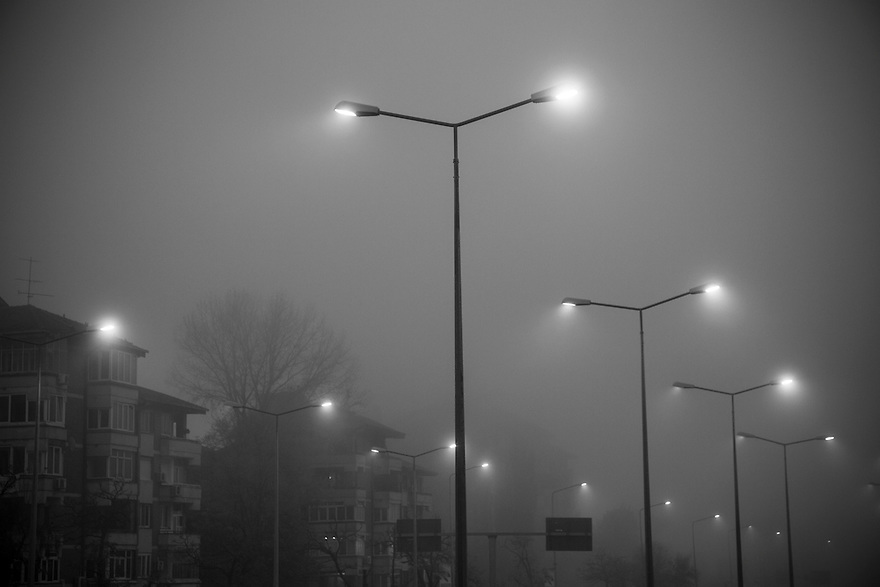 Street lights penetrate a deep fog in Bucharest, where winter is harsh for thousands of minors and young adults living in Bucharest's vast system of underground canals used for heating, water and sewage pipes.