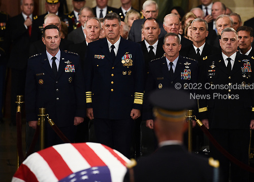 Members of the military stand at attention as they look at the flag-draped casket of former President George H.W. Bush inside the Rotunda in the US Capitol during the State Funeral in Washington, DC, December 3, 2018. - The body of the late former President George H.W. Bush travelled from Houston to Washington, where he will lie in state at the US Capitol through Wednesday morning. Bush, who died on November 30, will return to Houston for his funeral on Thursday. (Photo by Brendan SMIALOWSKI / AFP)