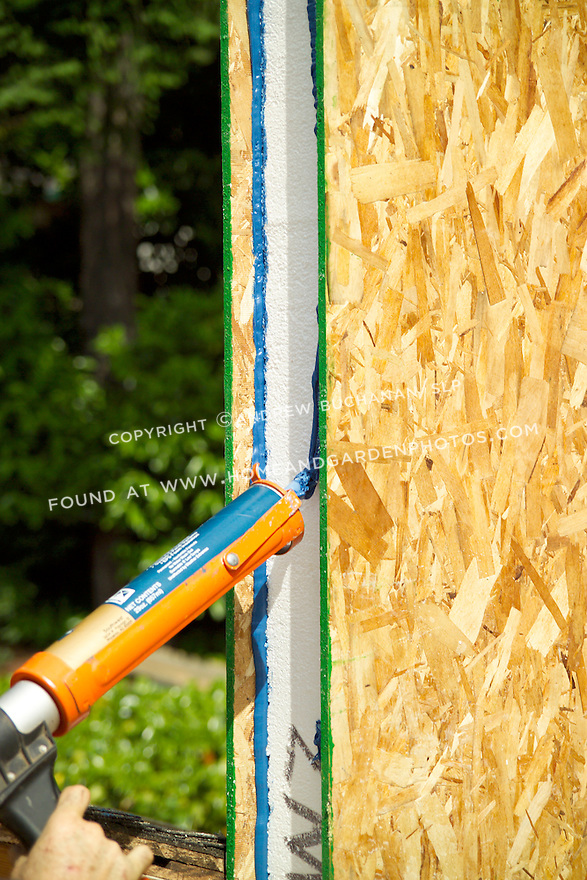 """Detail of adhesive being applied to the outer edge of a structurally insulated panel, or S.I.P., in preparation for joining it to another panel on a residential remodel project outside Seattle.  SIP's laminate a 6-8"""" thick layer of strofoam between two OSB boards in pre-fabricated shapes, thus combining framing, sheathing, and insulating into a single step."""