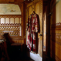 A kaftan hanging on the back of the bedroom door