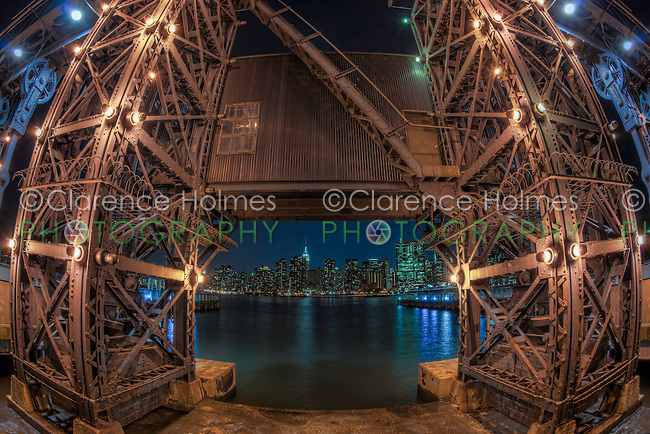 The Manhattan night skyline framed by one of the gantry cranes across the East River in Gantry Plaza State Park located in Long Island City, Queens, New York.    The restored cranes, dating from 1920, were used to load Long Island Railroad rail car floats with industrial goods.