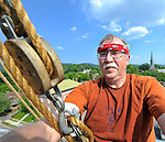 Bob Gathany / The Huntsville Times. Steeplejacks with Inspiring Heights work on covering the steeple of the First Methodist Church in downtown Huntsville with copper.  Bob on the steeple 110 feet above the ground.