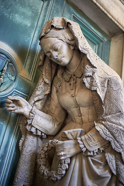 Picture and image of the stone sculpture of a  mourning widow who is bringing a crown and knocking on a sepulcher's bronze door, which holds the bas relief of an hourglass, a classic symbol of the passing of time. This theme of the sorrowful survivor in front of the sepulcher's door comes from the Monument dedicated to Maria Christina, Duchess of Teschen, Maria Theresa of Austria's daughter, a neoclassical sculpture. In this version the widow is wearing fashionable clothes, which have been accurately represented, and her openwork shawl. Sculptor G. B. Cevasco 1875. Section A, no 38, The monumental tombs of the Staglieno Monumental Cemetery, Genoa, Italy