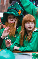 St Patricks Day parade High Street Digbeth.Crop Two Children waving from Parade float High St location around the Custard Factory