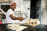 Yemeni man making local bread on skillet, Hawf Protected Area, Yemen
