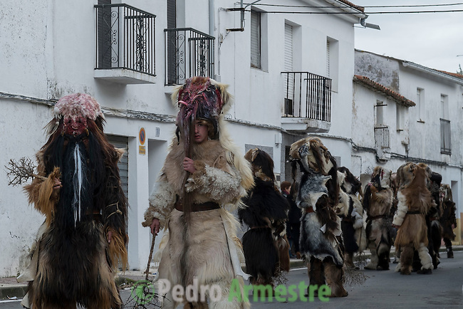 "Carantoñas waits before the procession during the Carantoñas festival, in Acehúche near Cáceres, on January 21, 2015. The ""Carantoñas"", monster-animal characters mixing paganism with Christianity, search for Saint Sebastian in the streets of the village of Acehúche, southwestern Estremadure province, dressed in patchwork sheep, cow, rabbit and goatskins under painted masks. Arriving eventually at the village church, a procession takes place with the statue of the patron saint. Until recently, Spain's neighbors, the Berbers of Morocco, preserved a version of the same ritual in their animal-hided winter ""goblin,"" Bou Inania.  © Pedro ARMESTRE"