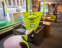 A costumed actor takes a break from his role as a TD Bank mascot in a new branch during its grand opening ceremonies in Midtown Manhattan on Friday, October 28, 2016. TD Bank has seen growth recently through expansion of its retail banking network and the acquisition of other banks. (© Richard B. Levine)