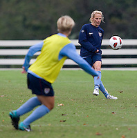 USWNT midfielder Kristine Lilly punts the ball over midfielder Lori Lindsey during practice in Chester, PA.  The USWNT will take on China, in an international friendly at PPL Park, on October 6.