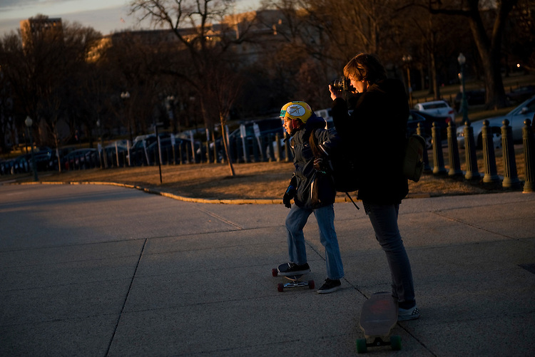 UNITED STATES - JANUARY 10:  Forrest Foster, 16, right, and Isaac Carroo, 13, of Capitol Hill, take a break from skateboarding on the Senate side of the Capitol, to observes the sun setting beyond the Mall. (Photo By Tom Williams/Roll Call)