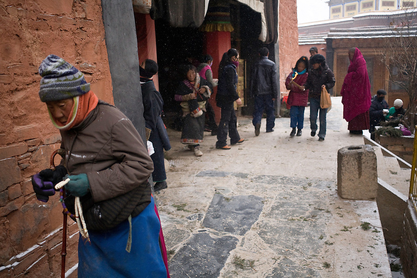 Some tibetan pilgrims are following the circumambulation path around the temple of Maitreya, the buddha of the future, in the monastery of Labrang for the anniversary of Tsongkhapa the founder of the Yellow hats order.
