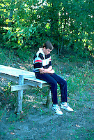 Age 16 teen, deep in thought, sitting on end of dock.  Mound Minnesota USA