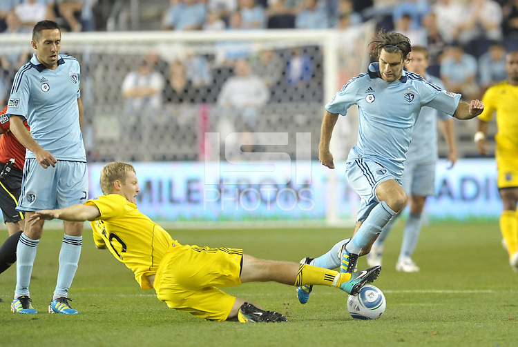 Columbus Cfrew midfielder Kevin Burns (15) attempts to tackle Sporting KC midfielder Graham Zusi (8)... Sporting Kansas City defeat Columbus Crew 2-1 at LIVESTRONG Sporting Park, Kansas City, Kansas.