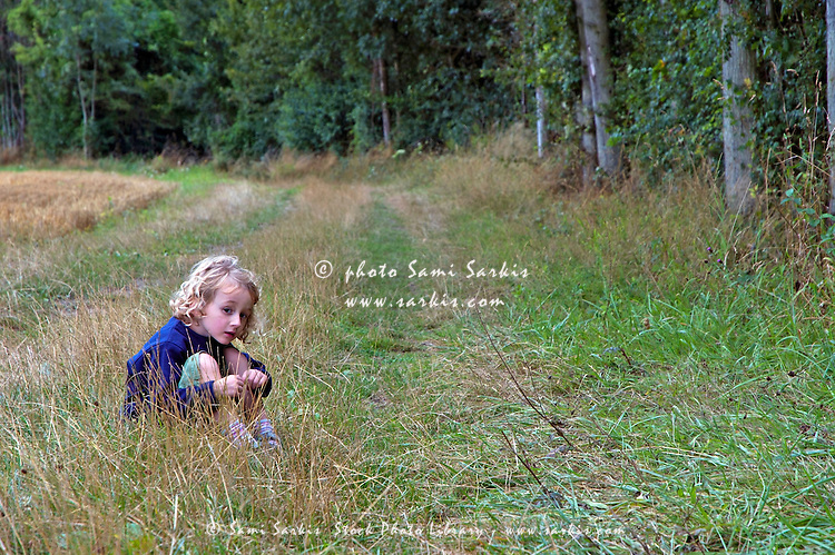 Four year old girl sitting alone in the grass beside a forest, France.