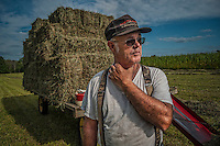 Sam Bigham stands next to a trailer loaded with fresh hay recently baled on his family's Westerville, OH, farm. Bigham's family has owned the farm since 1920 but recently signed a contingency contract to sell the land to a housing developer. It is the last working farm in the city.