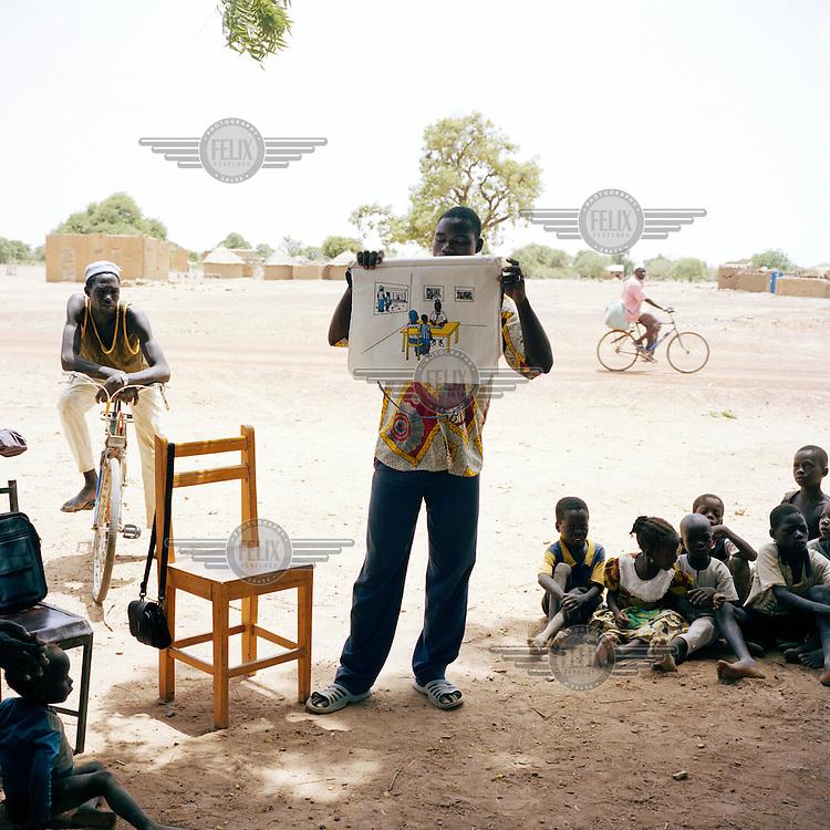 A man teaches children about malaria in a remote village in Namentenga.