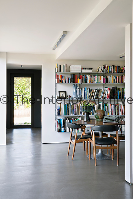 The library serves as an additional home office, complementing a separate study and design studio. The shelving is a classic Dieter Rams design. The chairs are mid-century Danish pieces and the table is vintage Eero Saarinen.